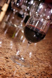 Glass of red wine. On brown granite bar with wine glasses in the background Royalty Free Stock Image
