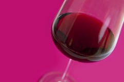Glass with red wine. On pink background Royalty Free Stock Photos
