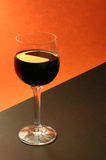 Glass of red wine. Or orange and black background Royalty Free Stock Images
