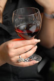 Glass with red wine. A glass filled with red wine in a female hand Royalty Free Stock Photo