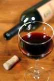 Glass of Red Wine. This is an image of a glass of red wine with a wine bottle in the background stock image