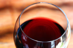 Glass of Red Wine. Closeup of a glass of red wine in natural light. Focus on front lip of glass stock photo