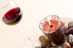 A glass of red wine (2). A glass of red wine next to a candle and stones Stock Image