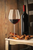 Glass of red wine. On a wooden chair, with dry leaves and a bottle of red wine on background Royalty Free Stock Image
