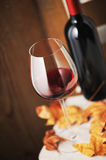Glass of red wine. And a bottle of red wine on background (shallow dof Royalty Free Stock Photo