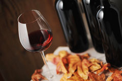 Glass of red wine. And a bottle of red wine on background (shallow dof Stock Image