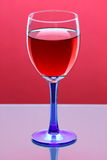 Glass of red wine. Against a colorful background Royalty Free Stock Image