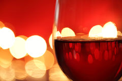 Glass of red wine against defocussed lights Royalty Free Stock Image