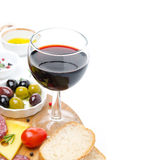 Glass of red wine and appetizers - cheese, bread, salami, olives stock photos