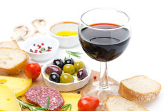 Glass of red wine and appetizers - cheese, bread, salami, olives Royalty Free Stock Images