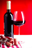 Glass of red wine. Is on the red background Stock Image