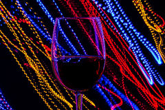 Glass of red wine on background of abstract colored lights in motion. Glass of red wine on a background of abstract colored lights in motion Stock Photos