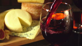 Glass of red wine on a background of cheese plate. Close-up of a glass of red wine on a background of a cheese plate near the fireplace stock footage