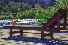 Glass of red wine on the background of a mountain river. Wooden chaise lounge, mountains, luxury holiday stock photos