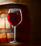 Glass of red wine. On the background of old barrel Royalty Free Stock Image