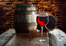 Glass of red wine. On the background of old barrels Stock Photography