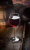 Glass of red wine. On the background of old barrels Royalty Free Stock Photography