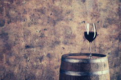 Glass of red wine on barrel. L Toned stock photos