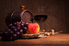 Glass of red wine and barrel on rustic wood tabel Royalty Free Stock Image