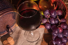 Glass of red wine and barrel on rustic wood tabel Stock Image