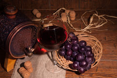 Glass of red wine and barrel on rustic wood tabel Royalty Free Stock Photo