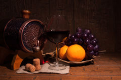 Glass of red wine and barrel on rustic wood tabel.  Royalty Free Stock Photo