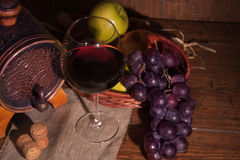 Glass of red wine and barrel on rustic wood tabel.  Stock Image