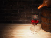 Glass of red wine and barrel on wooden table Royalty Free Stock Images