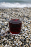 Glass of red wine on the beach. Closeup of glass of red wine on the beach royalty free stock photo