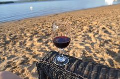 Glass of red wine on the beach. Glass of red wine on a great beach of Taureau Lake in Quebec, Canada royalty free stock photo
