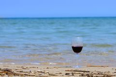 A glass of red wine on the beach seashore in summer on sunny day with blue sea. stock photo