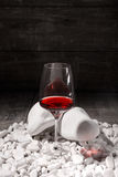 A glass of red wine on a black background. A beautiful wine glass full of a dry red liquid on decorative stones. Copy. A view from above on a glass full of dry Royalty Free Stock Photo
