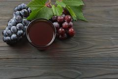 Glass of red wine with blue grapes and green leaf on dark wooden table. Top view with copy space Stock Image