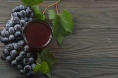 Glass of red wine with blue grapes and green leaf on dark wooden table. Top view with copy space Royalty Free Stock Image