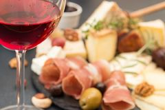 Glass of red wine and blur cheese plate with pieces moldy cheese. Prosciutto, pickled plums, olives, grapes, figs, honey, pear, nuts on black slate background stock photos
