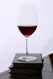 Glass of red wine on the books at wooden table against white backdrop Royalty Free Stock Photos