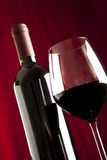A glass of red wine and a bottle Stock Images