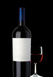 Glass of red wine with bottle. Glass of red wine on black background Stock Photo