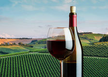 Glass of red wine with a bottle on the background of the rural l. Andscape of vineyards in Tuscany Stock Photography