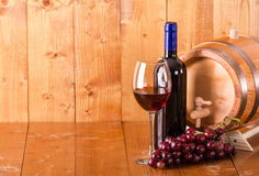 Glass of red wine bottle barrel and grapes. On  wooden background Stock Images