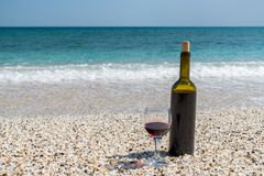Glass of red wine and bottle on the beach at the summer day. Glass of red wine and bottle on the beach at the summer sunny day. Sea on the background royalty free stock photos