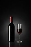 Glass of red wine and bottle. On a black background Royalty Free Stock Photos