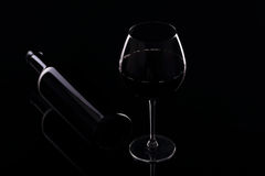 Glass with red wine and bottle. On the black mirror royalty free stock photo