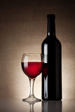 Glass of red wine with a bottle Stock Photography