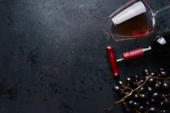 Glass with red wine, bottle with corkscrew and red grape clusters on black rustic background, top view. Place for your design Stock Images