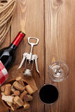 Glass of red wine, bottle and corkscrew on rustic wooden table Stock Photo