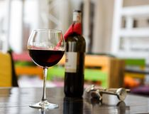 Glass of red wine with bottle and corkscrew on table in cafe.  Stock Image
