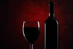Glass with red wine and bottle Royalty Free Stock Images