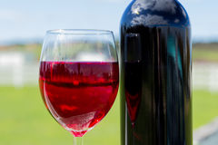 Glass of Red Wine and Bottle. A glasss of red wine and a bottle of wine with a blurred background Stock Photography