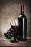 Glass of red wine with bottle and grape. On a brown background Royalty Free Stock Images